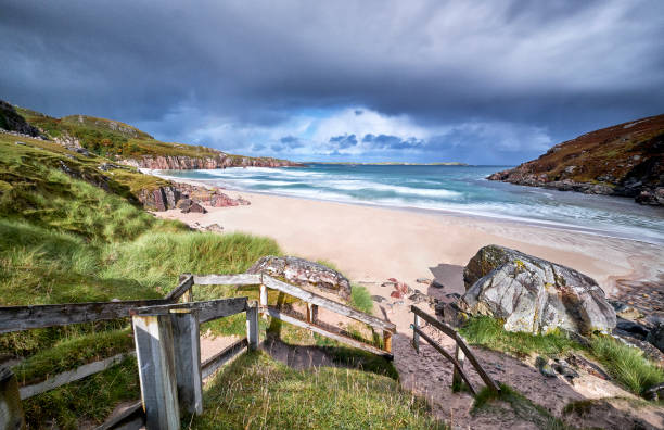 A beautiful small white beach. A beautiful small white beach in Scotland with azure blue water. There is a staircase between the grass and the rocks so that you can get to the beach. It is a cloudy day but the sun comes in occasionally. north coast 500 stock pictures, royalty-free photos & images