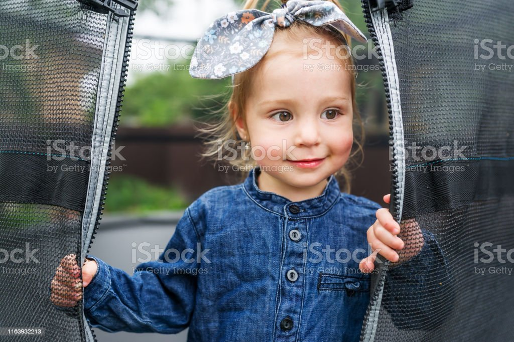 Beautiful little girl with bow is in the playground. Little girl...