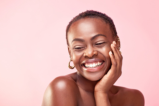 Studio shot of a beautiful young woman posing against a pink background