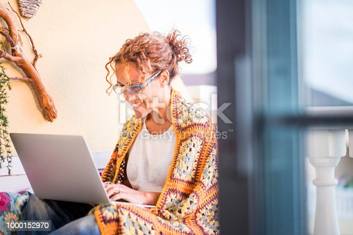 beautiful smiled caucasian woman work with a laptop computer outdoor in the terrace. alternative office and lifestyle working at home in totally freedom from the usual place where people works