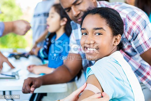 Beautiful smiling african american girl with a bandaid put on her arm. She is smiling directly at the camera. Her dad is standing beside her. There are kids blurry behind them who are getting health examinations before they get their flu shot or vaccinations.