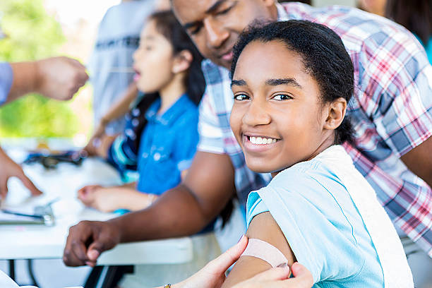 Beautiful smiling African American Girl after getting a flu shot Beautiful smiling african american girl with a bandaid put on her arm. She is smiling directly at the camera. Her dad is standing beside her. There are kids blurry behind them who are getting health examinations before they get their flu shot or vaccinations. tetanus stock pictures, royalty-free photos & images