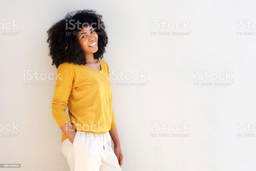 Belle femme afro-américaine souriante contre un mur blanc avec espace de copie - Photo