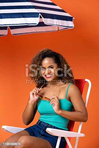 istock Beautiful smiling African American woman sitting on a beach chair 1155469874