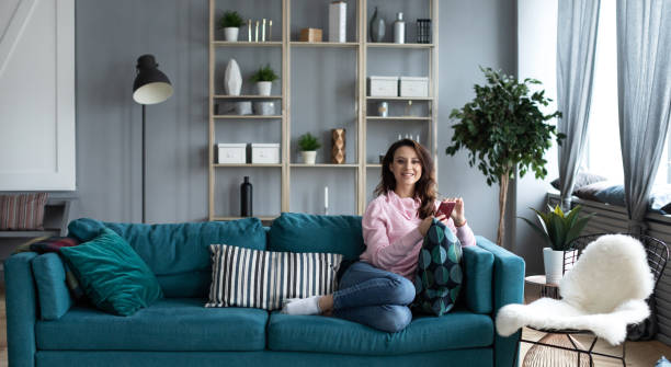 Beautiful smiling alone woman with smartphone on sofa in the interior of a living room. Use on mobile. stock photo