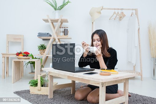 485539628 istock photo Beautiful smiling Asian student woman learning from online education service, Young Asian woman doing homework drinking cup of coffee 991392628