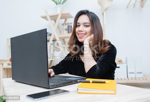485539628 istock photo Beautiful smiling Asian student woman learning from online education service, Young Asian woman doing homework with computer laptop , notebook and smart phone 991392632