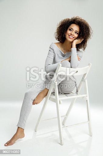 Beautiful black woman sitting on chair and dreaming