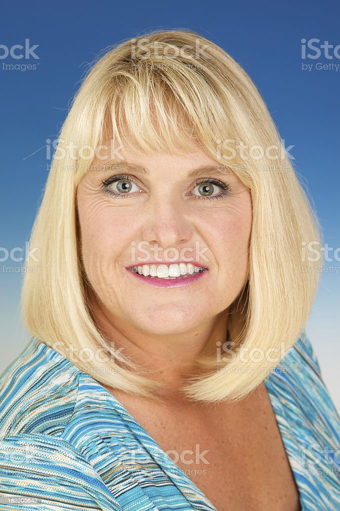 Beautiful Smiling Blond Forty Year Old Woman on Blue royalty-free stock photo