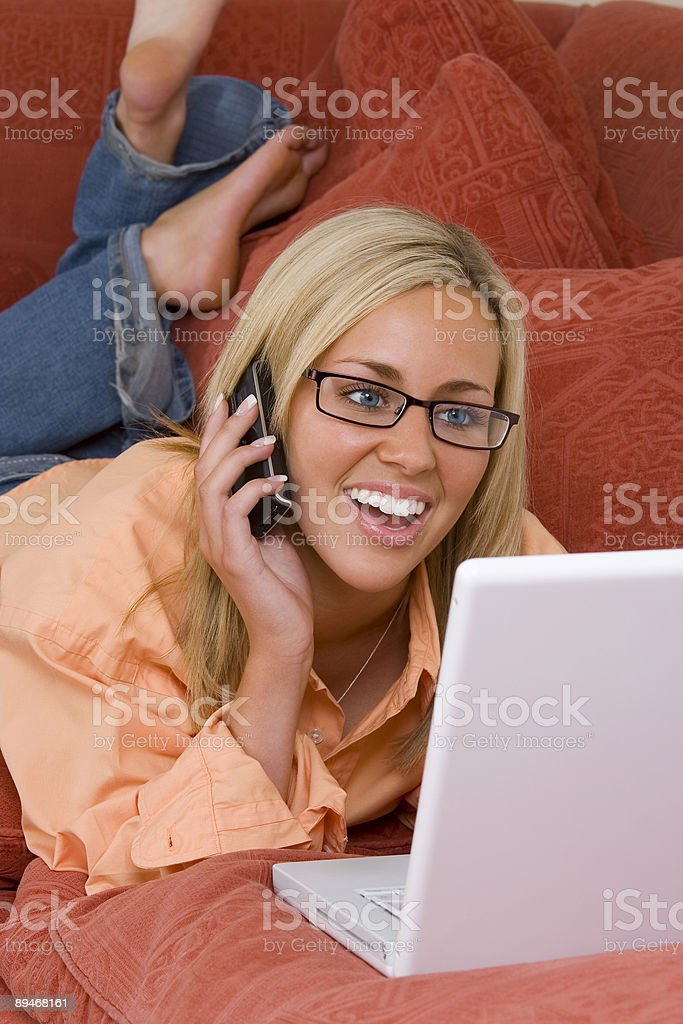 Beautiful Smiling Blond Girl On Cell Phone and Laptop Computer royalty-free stock photo