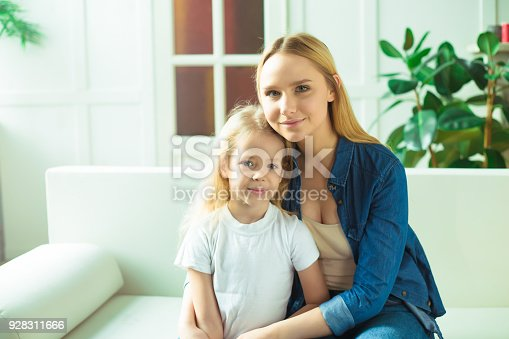641288086 istock photo Beautiful smiling blond mother and daughter embrace and have fun on the couch at home and look at the camera. Concept of mother and daughter. 928311666