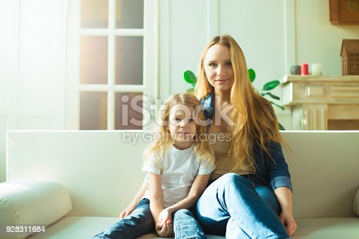 641288086 istock photo Beautiful smiling blond mother and daughter embrace and have fun on the couch at home and look at the camera. Concept of mother and daughter. 928311684