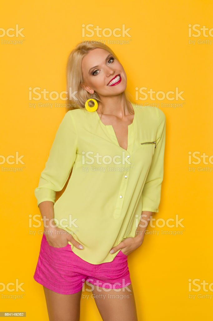 Beautiful Smiling Blond Woman In Yellow Shirt And Pink Shorts royalty-free stock photo