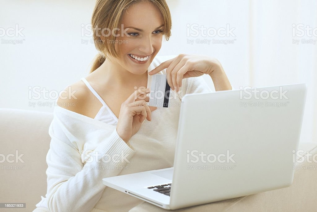Beautiful smiling blond woman, shopping online from home stock photo
