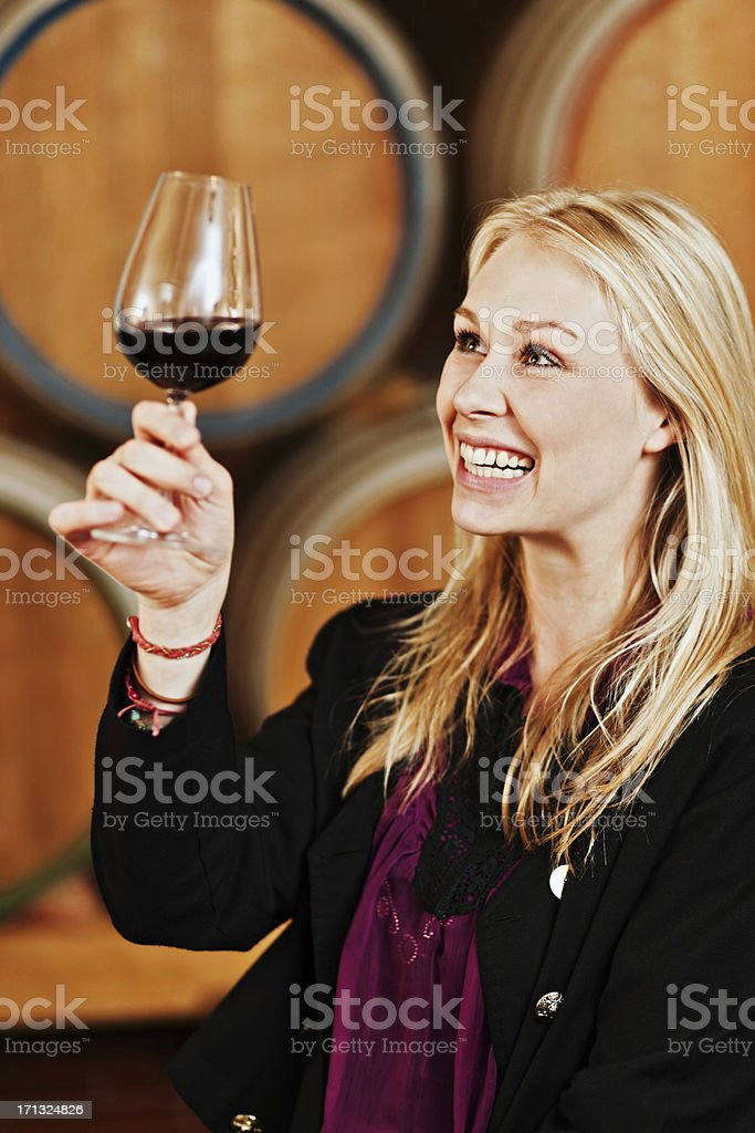 Beautiful, smiling blonde winestasting in winery cellar royalty-free stock photo