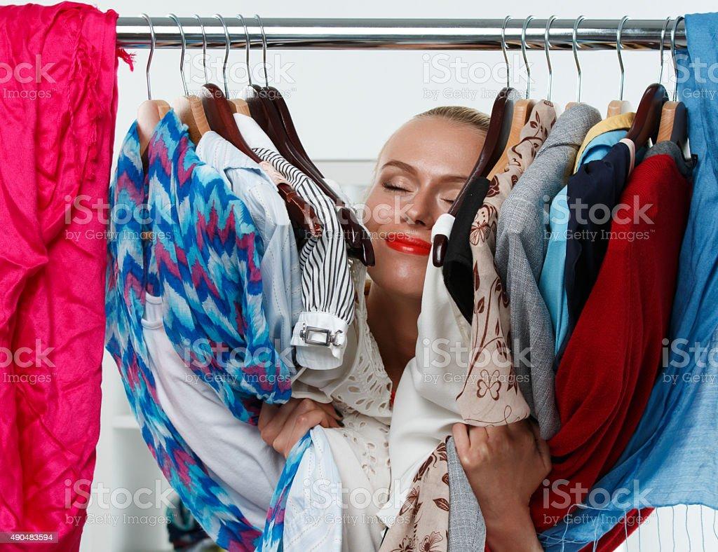 Beautiful smiling blonde woman standing inside wardrobe rack stock photo