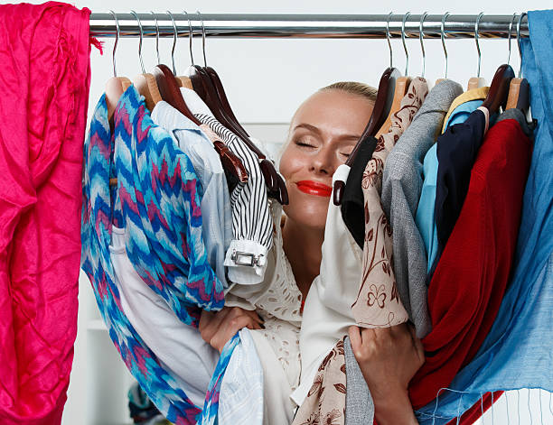 Beautiful smiling blonde woman standing inside wardrobe rack stock photo