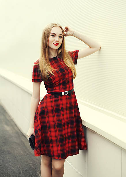 Beautiful smiling blonde woman wearing red checkered dress in city stock photo