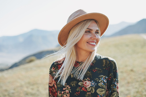 Beautiful smiling blone young woman traveler in dress and felt hat on road, trip to mountains, Altai