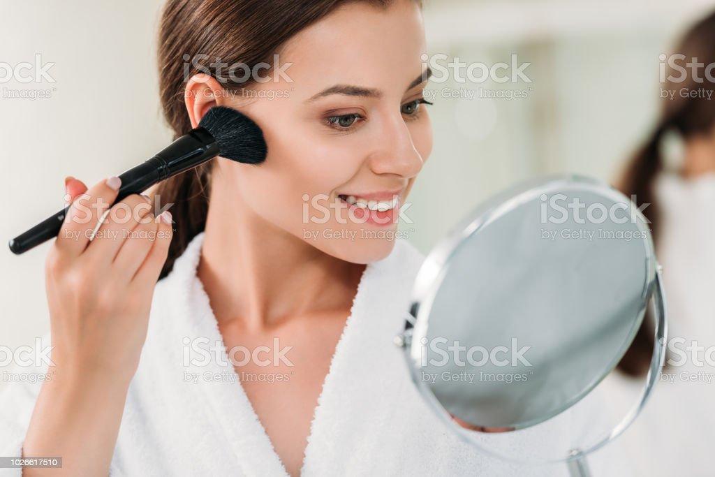 beautiful smiling brunette girl in bathrobe applying powder bronzer with brush stock photo
