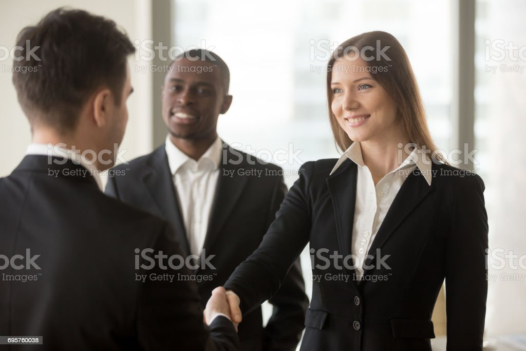 Beautiful smiling businesswoman and businessman handshaking, first impression, being promoted stock photo