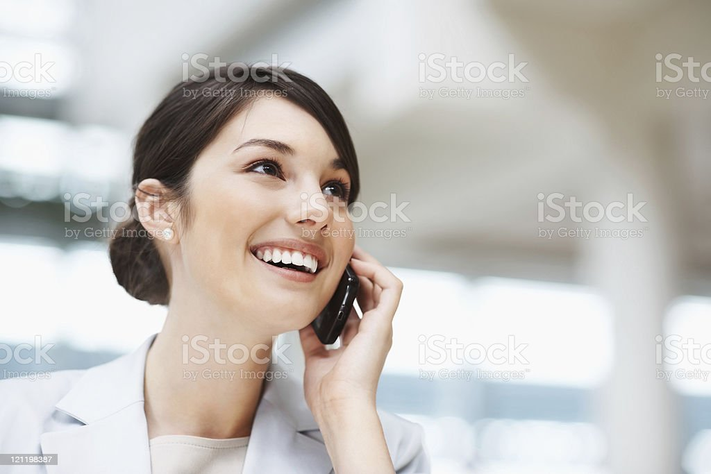 Beautiful smiling businesswoman talking on a cellphone Closeup of a beautiful smiling businesswoman talking on a cellphone 20-24 Years Stock Photo