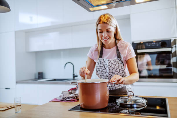 beautiful smiling caucasian blond young woman in apron standing in kitchen and stirring soup in pot. - cooker happy imagens e fotografias de stock