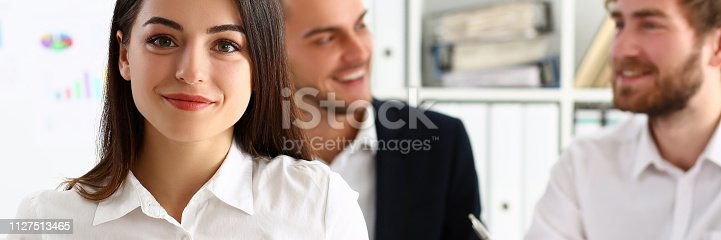 istock Beautiful smiling cheerful girl at workplace look 1127513465