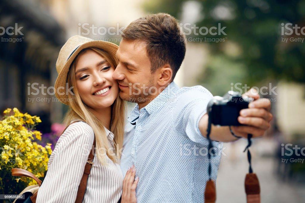Bella sonriente pareja divertido viajar, tomar fotos - Foto de stock de Abrazar libre de derechos