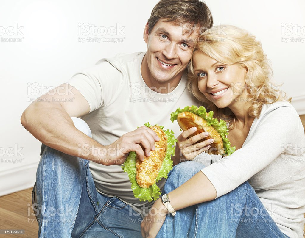 Beautiful smiling couple having lunch sitting on floor. royalty-free stock photo