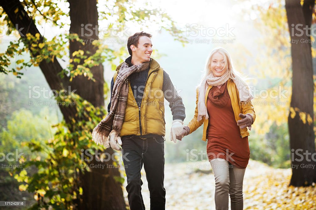 Beautiful smiling couple running in the park royalty-free stock photo