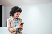 istock Beautiful smiling curly-haired businesswoman using smarphone indoors, copy space. 1139864018