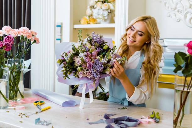 beau fleuriste féminin de sourire dans le tablier organisant le bouquet dans la boutique de fleurs - fleuriste photos et images de collection