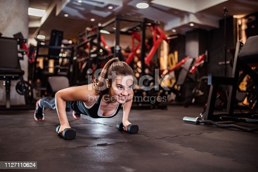 Beautiful smiling girl doing push-up on weights.