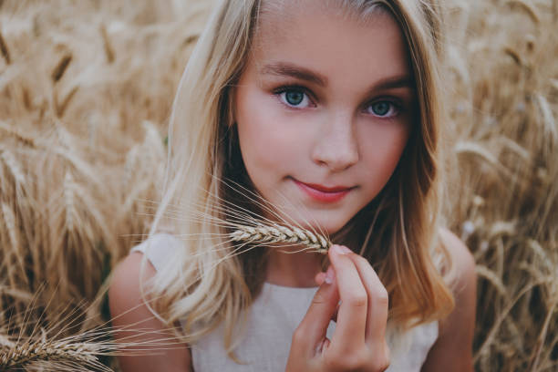 Beautiful smiling girl in a wheat field. stock photo