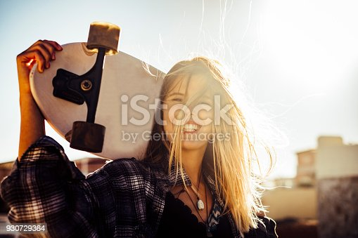 istock beautiful smiling girl in backlight with skateboard 930729364