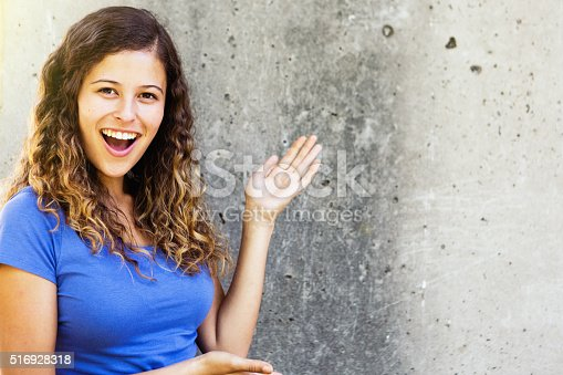This beautiful young honey-blonde woman smiles happily as she points out a blank space - ready for your message - on a grungy grey wall.