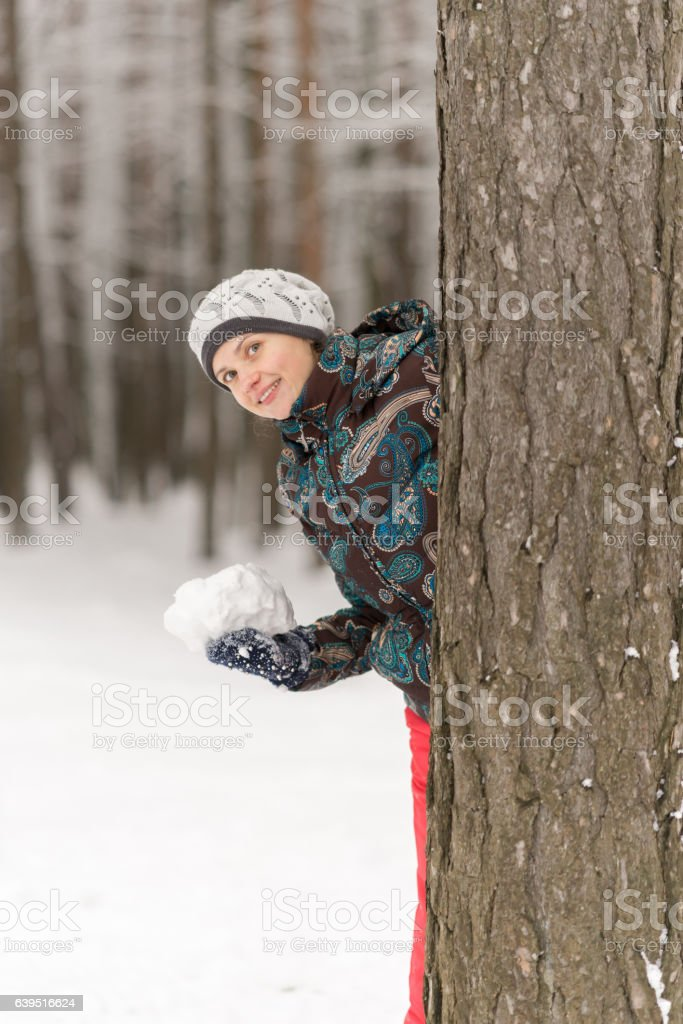 Beautiful smiling girl playing in the snow and preparing to stock photo