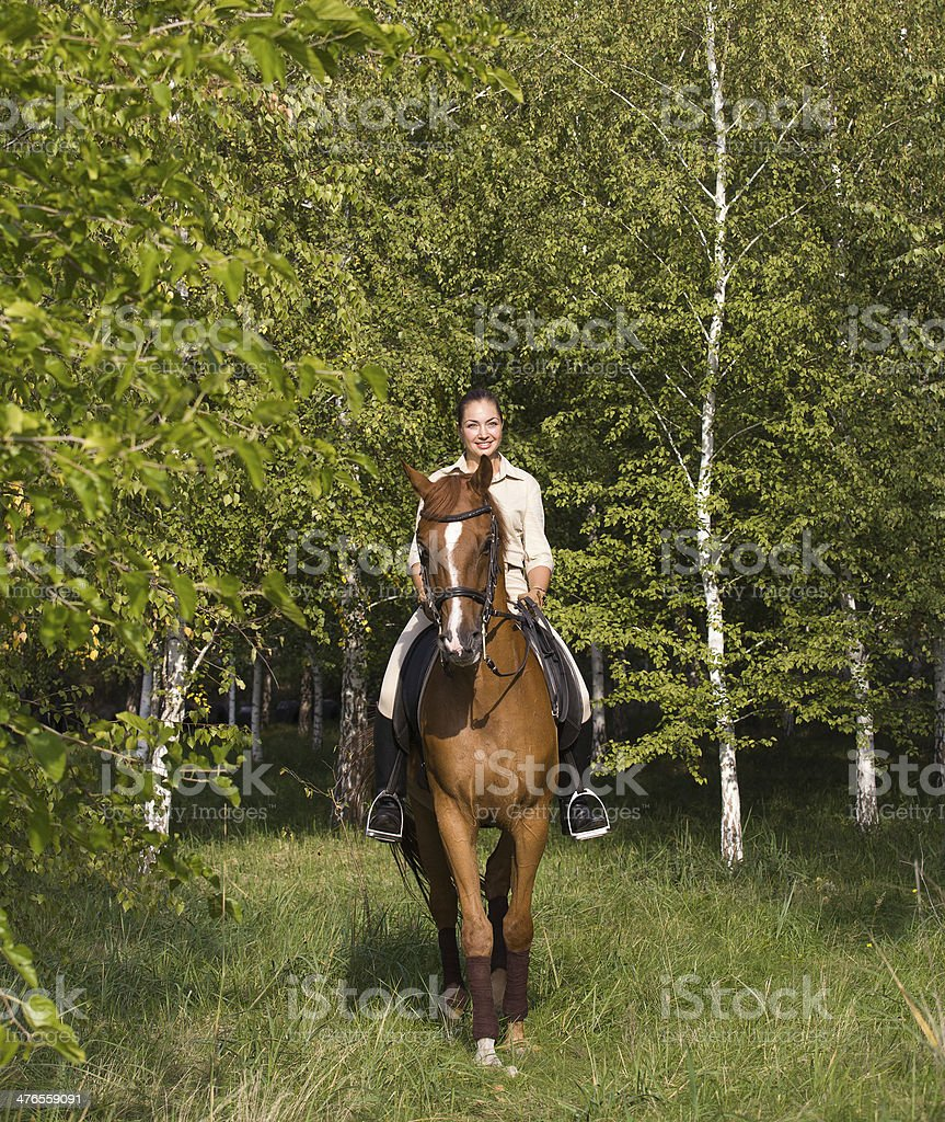 Beautiful smiling girl riding a brown horse through woodland royalty-free stock photo