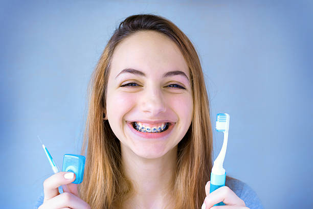 Beautiful smiling girl with retainer for teeth brushing teeth . stock photo