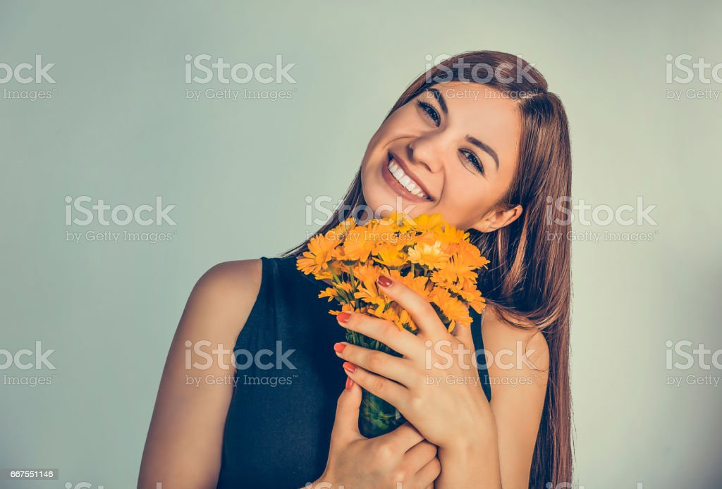 Beautiful smiling girl, woman holding bouquet of marigold, calendula. Young smiley cute female lady smelling flowers isolated on green background wall. Positive facial expression human emotion feeling - foto de acervo