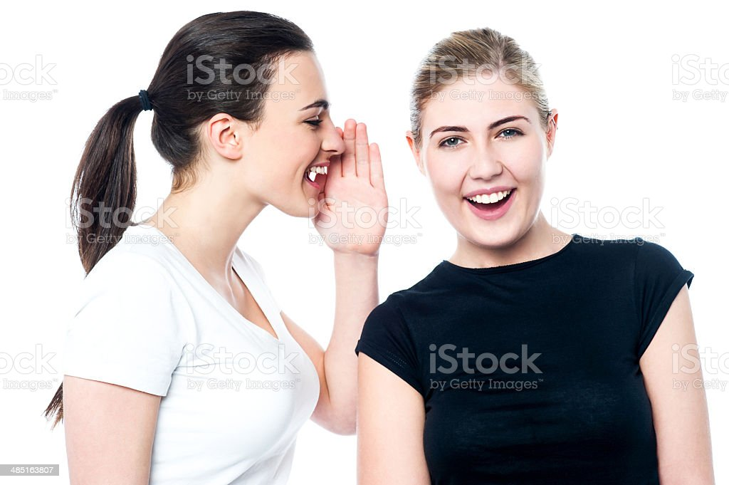 Beautiful smiling girls sharing a secret stock photo