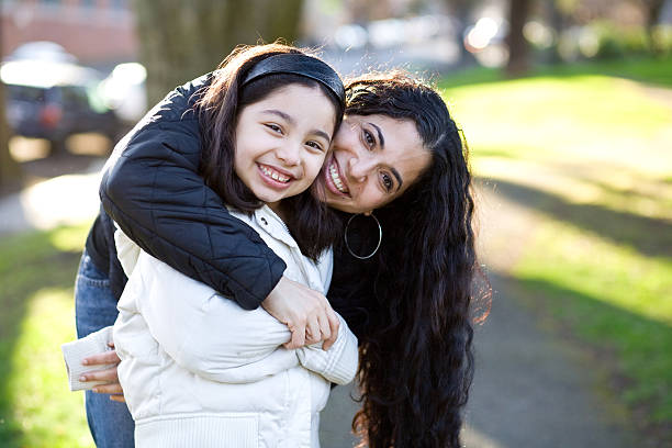 beautiful smiling hispanic mother and daughter hugging in a park stock photo