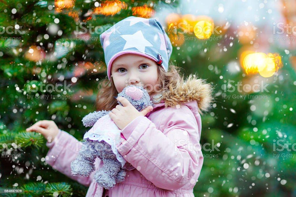 beautiful smiling little girl holding christmas tree stock photo