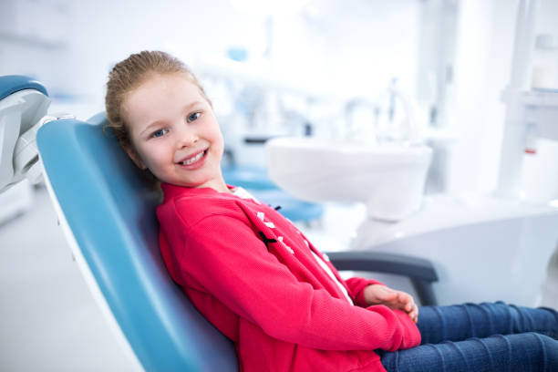 beautiful smiling little girl in dental office - dentist stock photos and pictures