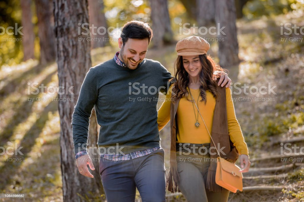 Beautiful smiling love couple walking in colorful autumn forest park stock photo
