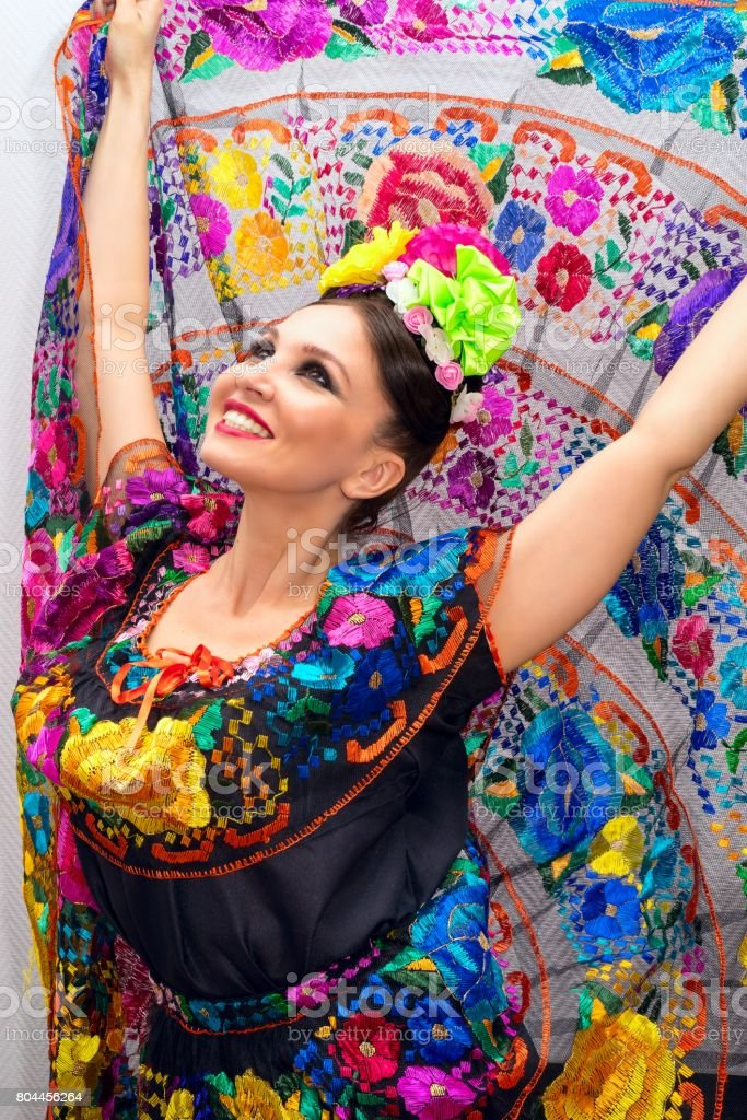 beautiful smiling mexican woman in traditional mexican dress nands up holding the skirt as a background like peacock stock photo