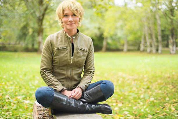 beautiful, smiling, mid 30's woman sitting cross-legged. - 30 39 jaar stockfoto's en -beelden