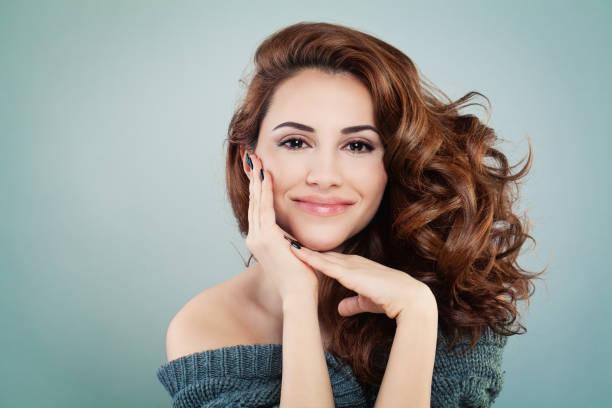 hermosa mujer modelo sonriente con peinado ondulado. cosmetología y tratamiento concepto - hair woman fotografías e imágenes de stock