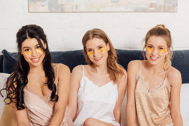 beautiful smiling multicultural girls with golden eye patches looking at camera in bed during pajama party beautiful smiling multicultural girls with golden eye patches looking at camera in bed during pajama party costume eye patch stock pictures, royalty-free photos & images